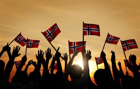 gente saludando: Grupo de personas que ondeaban banderas noruegas en Contraluz