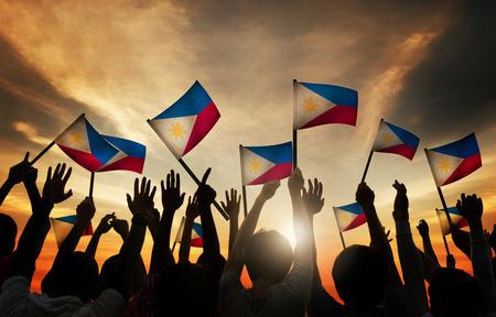 gente saludando: Grupo de personas que ondeaban banderas filipinas en Contraluz