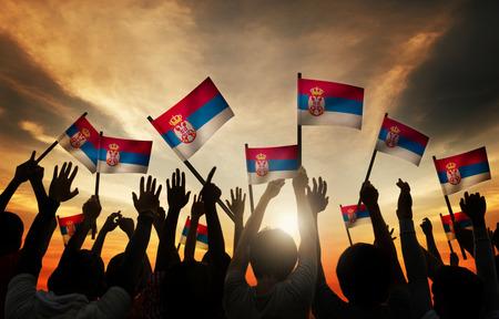 back lit: Group of People Waving Flag of Serbia in Back Lit