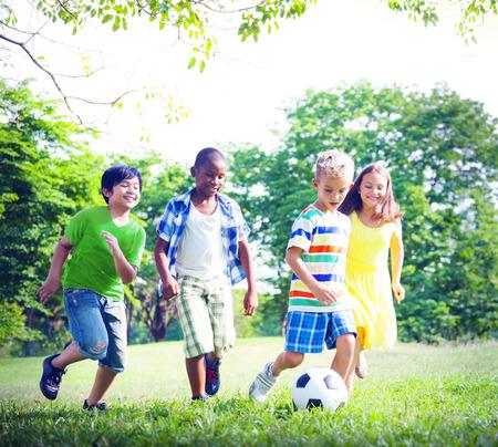 Niños jugando fútbol en el parque. Foto de archivo