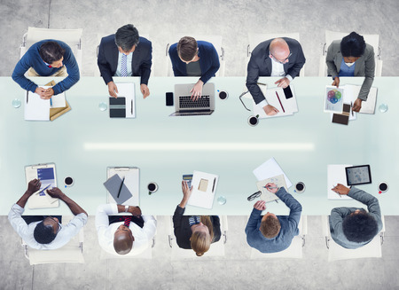 medium group of people: Business People Working Around a Conference Table Stock Photo