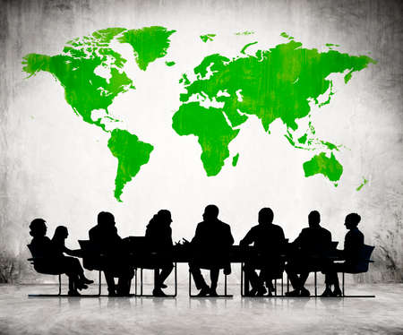 coworker: Business People Discussing Around The Conference Table And A Green Cartography Of The World Above