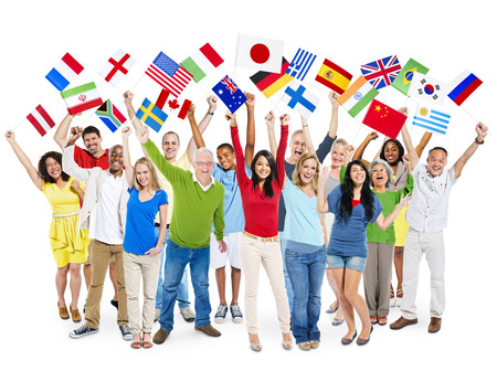 global village: Cheerful Multi-Ethnic Group Of People Standing With Their Arms Raised Holding World Flags. Stock Photo
