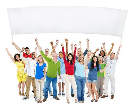 personas de pie: Grupo multi�tnico de personas casuales con los brazos levantados y que sostiene la bandera vac�a durante un espacio de la copia.
