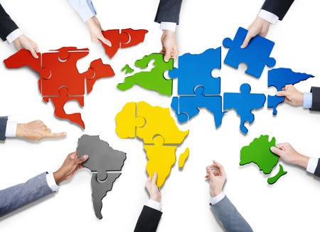 mundo manos: Grupo de hombres de negocios con Jigsaw Puzzle Formando en Mapa del Mundo