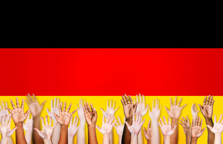 german ethnicity: Group of Multi-Ethnic Arms Raised and a Flag of Germany as a Background