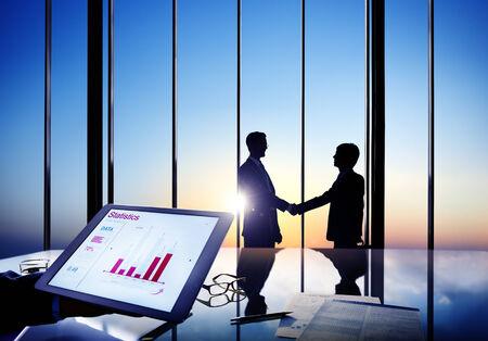 contrato de trabajo: Siluetas de dos hombres de negocios que sacuden las manos juntas en una sala de juntas Foto de archivo