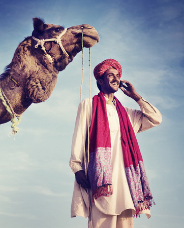 indian summer seasons: Indian Man On the Phone Camel Communication Concept