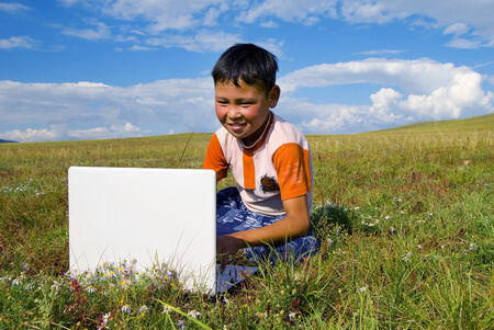 independent mongolia: Mongolian boy with laptop on grass.