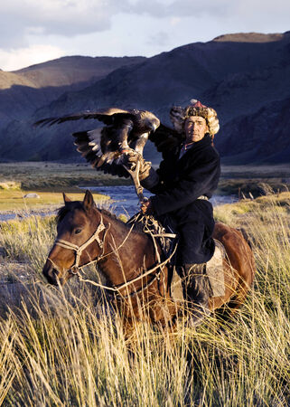 independent mongolia: Kazakh men traditionally hunt foxes and wolves using trained golden eagles.  Stock Photo