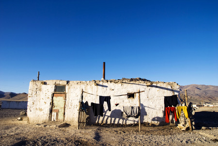 independent mongolia: Old weathered house with mountain range at the background.