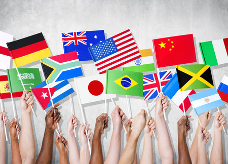 Grupo de manos que sostienen banderas nacionales.