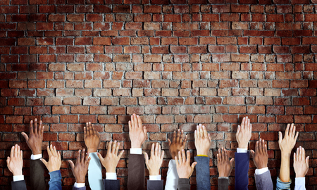 hands raised: Group of Diverse Business Hands Raised on Brick Wall