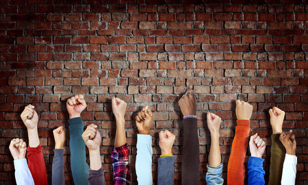 hands raised: Group of Diverse Hands Raised on Brick Wall