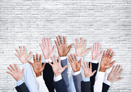 Group of business human arms raised with brick wall. photo