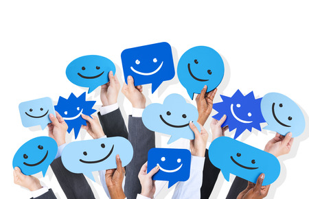 muti: Hands holding smiley faces icons. Stock Photo