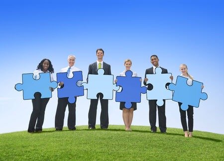 Business People Holding Jigsaw Puzzle Pieces Outdoors photo