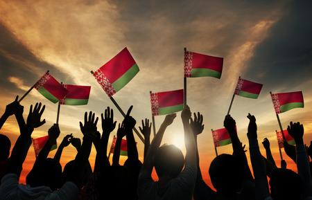 belarusian ethnicity: Siluetas de personas que tienen la bandera de Bielorrusia Foto de archivo