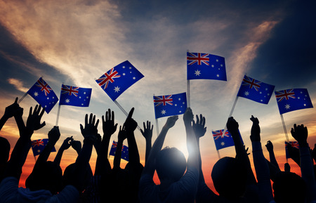 australian flag: Group of People Waving Australian Flags in Back Lit Stock Photo