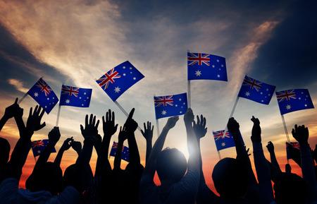 gente saludando: Grupo de personas que ondeaban banderas australianas en Contraluz