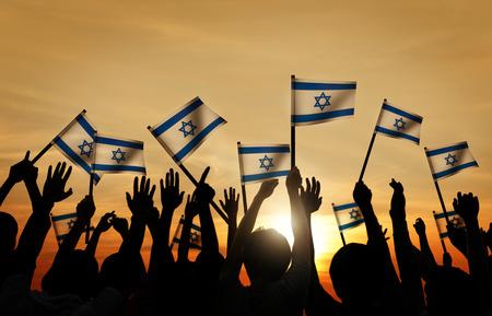 gente saludando: Siluetas de personas que ondeaban la bandera de Israel Foto de archivo