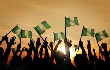 gente saludando: Grupo de personas que ondeaban la bandera de Nigeria en Contraluz