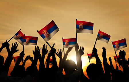gente saludando: Grupo de personas que ondeaban la bandera de Serbia en Contraluz Foto de archivo