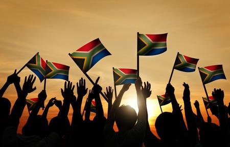 mujeres africanas: Grupo de personas que ondeaban banderas sudafricanas en Contraluz Foto de archivo