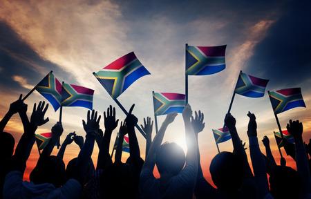 gente saludando: Grupo de personas que ondeaban banderas sudafricanas en Contraluz Foto de archivo