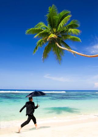 Businessman running at the beach. photo