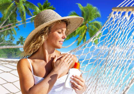 sun protection: Woman applaying sun protection on skin. Stock Photo