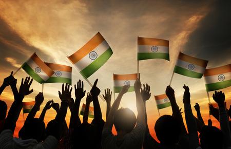 バックライトにインドの旗を振る人のグループ