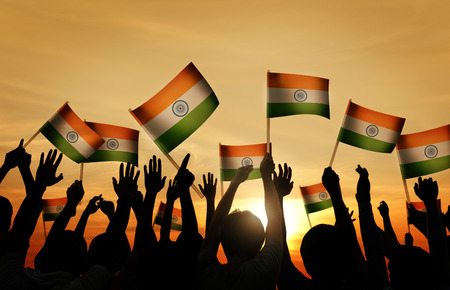 Group of People Waving Indian Flags in Back Lit photo