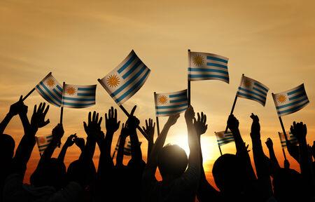 gente saludando: Grupo de personas que ondeaban banderas uruguayas en Contraluz