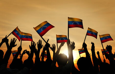 gente saludando: Grupo de personas que ondeaban banderas venezolanas en Contraluz