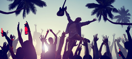 Silhouettes of People Enjoying a Concert on the Beach photo