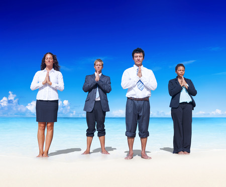 meditate: Business people meditating on the beach.