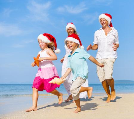 Familia que se ejecuta en la playa de la Navidad. Foto de archivo - 34406751