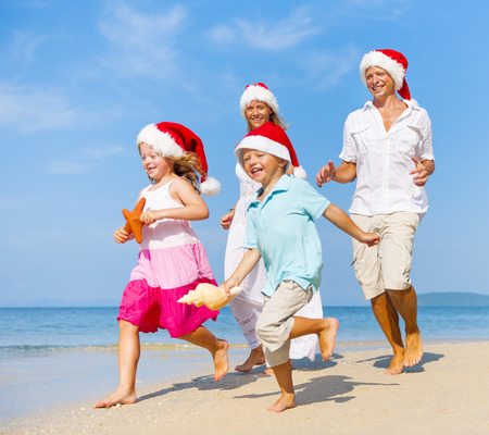 Family running on the beach in Christmas. Stock Photo