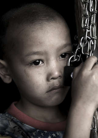 clasping: Sad child clasping a lock and chain.