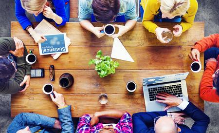 reuniones empresariales: Grupo de hombres de negocios que discuten en un caf�