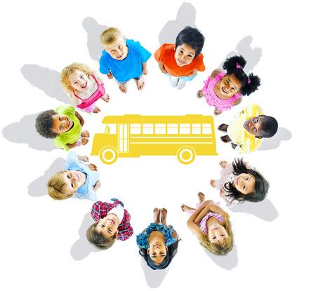 niños en la escuela: Grupo multiétnico de Niños y autobús escolar