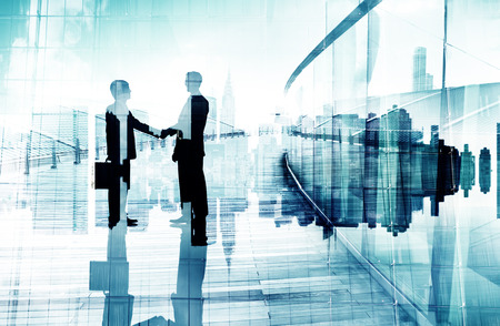 international business agreement: Silhouettes of Two Businessmen Having a Handshake