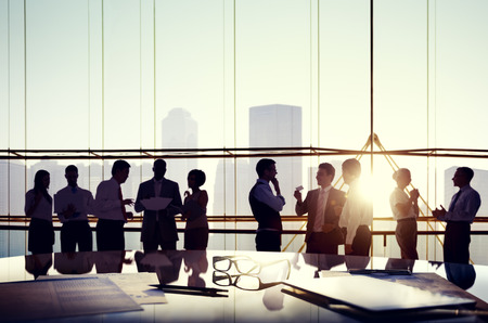 business building: Group of business people discussing at sunset reflected onto table with documents. Stock Photo