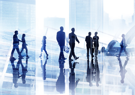 Silhouettes of Business People Wllking Inside the Offce Stock Photo