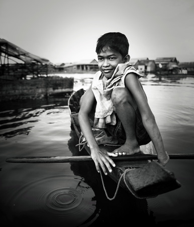 Boy traveling by boat in floating village. photo