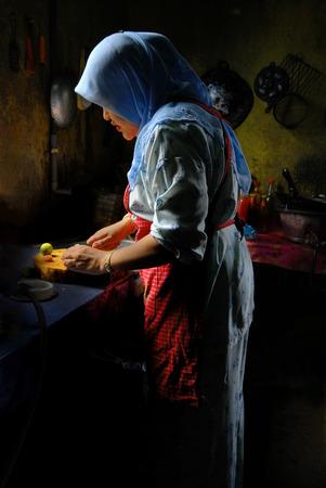 マレーシアの女性が自然な日光を使用して、台所で食べ物を準備します。