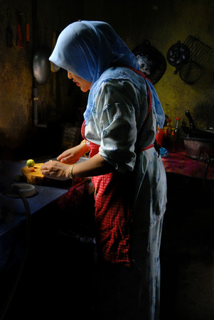 Malaysian lady using natural sunlight to prepare food in the kitchen.