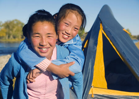 independent mongolia: Happy Mongolian girls playing piggyback at campsite. Stock Photo