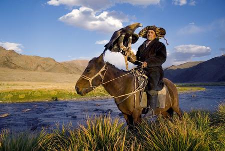 the hunter: Hombres kazajos tradicionalmente cazan zorros y lobos utilizando �guilas reales formados. Olgei, Mongolia occidental. He tenido la suerte de haber sido testigo de muchos lugares hermosos como fot�grafo. Cuando se toman muy bien Stock Art o aut�ntica fotograf�a de viajes que endeavo Foto de archivo